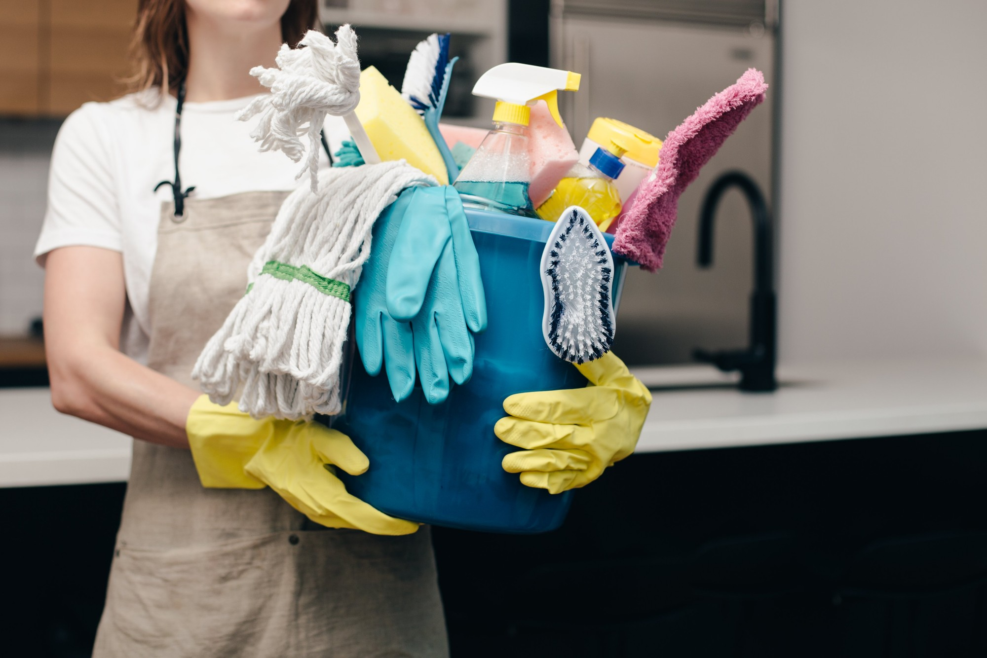 holding bucket of cleaning supplies
